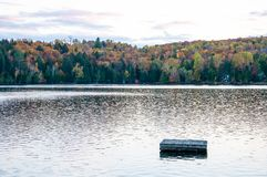 Sunset over lake with dock during Indian Summer in Quebec, Canada. Sunset over lake with trees and dock during Indian Summer in Quebec, Canada Royalty Free Stock Images