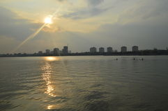 Sunset over lake in a city. Kayakers on a lake in Hanoi, Vietnam in the evening during sunset stock photos