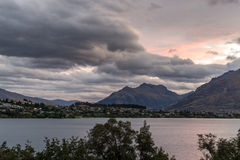 Sunset over lake wakatipu. With kelvin heights in the distance. Sunlight covered in stormy clouds. TAken during summer Stock Photo