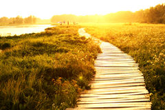 Sunset over lake and walkway Royalty Free Stock Images