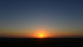 Sunset over Land. View of a Beautiful Sunset and Clear Sky over a Silhouetted Land Horizon Stock Photo