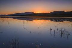Sunset over a large mountain lake. Stock Photos