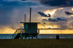 Sunset over a lifeguard tower and the Pacific Ocean  Stock Photo