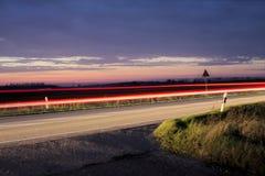 Sunset Over Lights. Sunset over a federal road (Bundesstrasse) near Greifswald, Mecklenburg-Vorpommern, Germany. Long exposure makes the movement of car lights royalty free stock photo