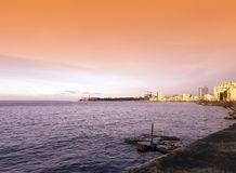 Sunset over Malecon and Atlantic Ocean with Morro Castle and residential building in background. Havana, Cuba Royalty Free Stock Photography