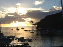 Sunset over Marigot Bay St Lucia. Sun rays strike the bay of Marigot Bay in St Lucia as boats sail in to dock for the day Stock Images