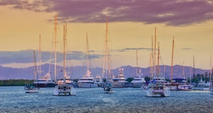 Sunset over the marina. Superyachts, motoryachts & Sailboats populate a tranquil marina at Port Denarau in Fiji, as the sun falls from the summer sky. Rich Stock Photos