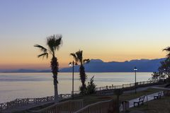 Sunset over the Mediterranean Sea. Palm trees and mountains against the sunset sky royalty free stock images