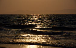 Sunset over the mediterranean sea. Reflections on the waves in the distance you can see the top of turkey Stock Photos
