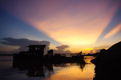Sunset over the Mekong with a wreck boat and geometrical clouds Royalty Free Stock Images