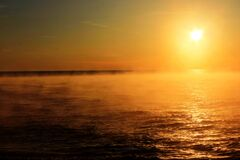 Sunset Over a Mist Covered Ocean Royalty Free Stock Photography