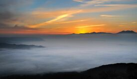 Sunset over misty mountains Stock Image