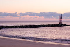 Sunset over mole on beach Royalty Free Stock Photography