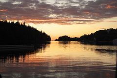 Sunset over Monastirskaya bay. Island Valaam Monastery Bay. The sky is painted last rays of the sun, reflected in the calm water Royalty Free Stock Image