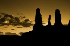 Sunset over Monument Valley. Scenic view of golden sunset over Monument Valley with Three Sisters rock formations silhouetted in foreground, Arizona, U.S.A Royalty Free Stock Photo