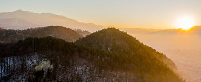 Sunset over the mountain. With a forest in the foreground stock photo