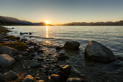 Sunset over a mountain lake Stock Images