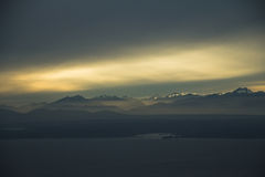 Sunset over Mountain Range. Sun sets between the clouds over the Olympic Mountain Range in Washington Royalty Free Stock Photos