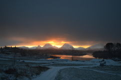 Sunset over mountain range. Overlooking fjord Stock Images