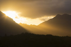 Sunset over mountain range with striking rays of s Royalty Free Stock Images