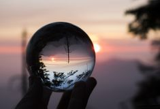 Sunset over Mountain Range with Trees in Silhouette Captured in. Sunset over California`s Sierra Nevada mountains captured in glass ball reflection with trees in stock photo