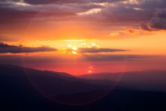Sunset over mountain tops with clouds. Sunset over Retezat mountain tops in Romania, Europe with clouds Stock Photos