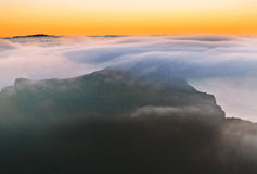 Sunset over the mountains in the clouds Stock Photo