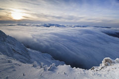 Sunset over the mountains and clouds in winter Stock Images