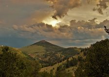 Sunset over Mountains in Cripple Creek. The setting sun glows behind clouds over the mountains just outside the small town of Cripple Creek, Colorado Stock Images