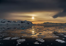 Sunset over the mountains and drifting icebergs at Lemaire Strai Stock Image