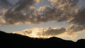 Sunset over the mountains, evening clouds fast moving away. timelapse.  stock footage