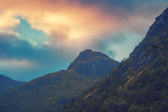 Sunset over mountains. Evening cloudy sky over mountains peaks Stock Photo