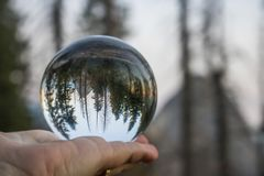 Sunset over Mountains with Forest and Moon Captured in Glass Ball Held in Palm. Mountain, forest and sunset sky with moon captured in glass ball reflection held royalty free stock photography