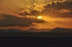 Sunset over the mountains with sun shining through the clouds royalty free stock photo
