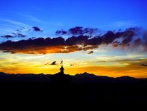 Sunset over mountains and weather vain. Bright sunset over rocky mountains and barn with weather vain rooster silhouette Stock Photo