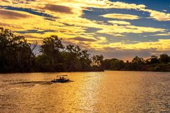 Sunset over Murray river with a boat in Mildura, Australia. Sunset over Murray river with people riding a boat in Mildura, Australia royalty free stock photography