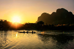 Sunset over Nam Song River with silhouetted rock formations and. A boat in Vang Vieng, Laos. Vang Vieng is a popular destination for adventure tourism in a Royalty Free Stock Photo