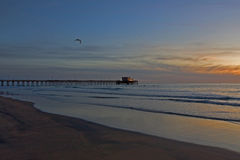 Sunset over Newport pier. Scenic view of sunset over Newport pier with sea and beach in foreground, California, U.S.A royalty free stock photography