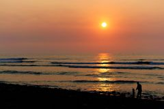 Coastal sunset with family of one adult and one small child in silhouette. Sunset over north Peruvian Pacific coast with a family of one adult and one small Royalty Free Stock Images