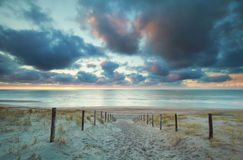 Sunset over North sea beach and sand path on dunes Royalty Free Stock Photos