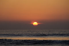 Sunset over the ocean. A picture of the red sun, as it sets over the calm ocean waters Stock Photo