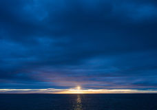 Sunset over Ocean on a Dark Cloudy Evening Royalty Free Stock Photography