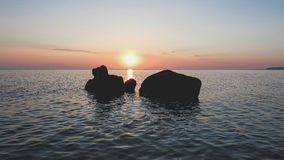 Sunset over Ocean With Large Boulders Stock Image