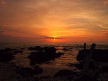 Sunset over ocean with lava rocks of Holoholokai Beach in the fo Stock Photos