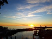 Sunset over ocean and marina. Sunset on calm ocean and marina Stock Photo