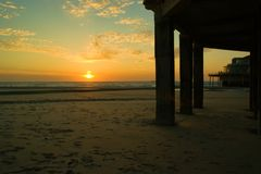 Sunset over the ocean with pier in blankenberge royalty free stock photo