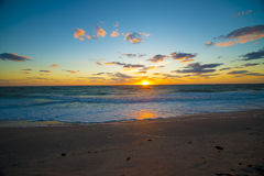 Sunset over the ocean with rolling waves. Beach sunset over ocean with waves rolling in Royalty Free Stock Image