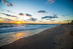Sunset over the ocean with rolling waves. Looking down coast line Beach sunset over ocean with waves rolling in Stock Photo