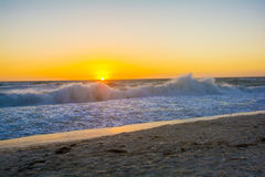 Sunset over the ocean with rolling waves. Sunset over ocean with waves rolling in splashing on the sandy beach Stock Photo