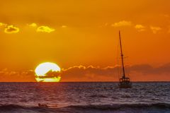 Sunset Over the Ocean with Sail Boat and Surfer in Maui HawaiiSunset royalty free stock photo